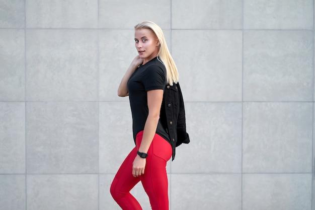 Ritratto di giovane attraente ragazza sportiva o modello che indossa abbigliamento sportivo nero, leggings rossi alla moda. colpo all'aperto sul fondo grigio della parete.