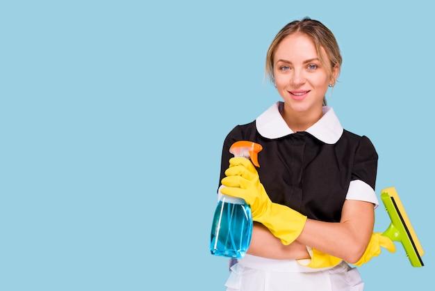 Ritratto di giovane attrezzatura per la pulizia graziosa dalla tenuta della donna che esamina macchina fotografica