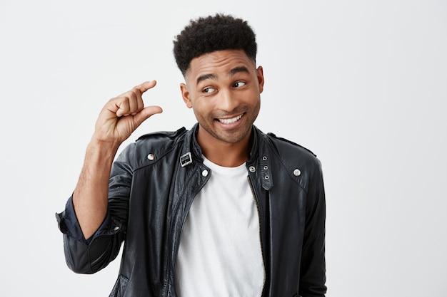 Ritratto di giovane bell'uomo divertente dalla pelle scura con acconciatura afro in maglietta bianca e giacca di pelle che gesticola con la mano, mostrando piccole dimensioni guardando da parte con l'espressione cinica del viso.