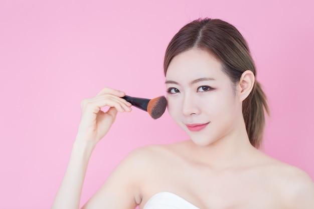 Ritratto di giovane bella donna asiatica caucasica che applica la polvere cosmetica della spazzola
