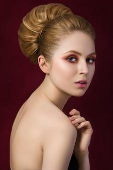 Ritratto di giovane bella donna bionda guardando indietro e toccando la sua spalla