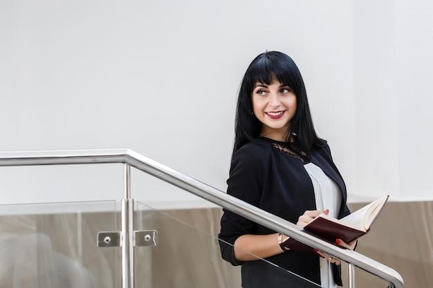 Ritratto di giovane bella donna bruna felice vestita in un tailleur nero, lavorando con un notebook, in piedi in ufficio, sorridente.