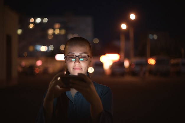 Ritratto di giovane bella donna caucasica che utilizza la stretta della mano dello smart phone all'aperto nella notte della città