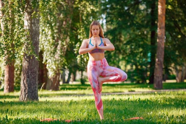Ritratto di giovane bella donna caucasica in una posa yoga sull'erba nel parco