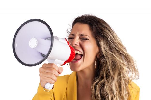 Ritratto di giovane bella donna che grida su un megafono isolato su bianco