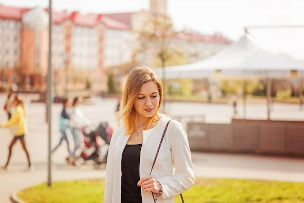 Ritratto di giovane bella donna che sorride alla macchina fotografica in città sul fondo bulding nel giorno di molla soleggiato