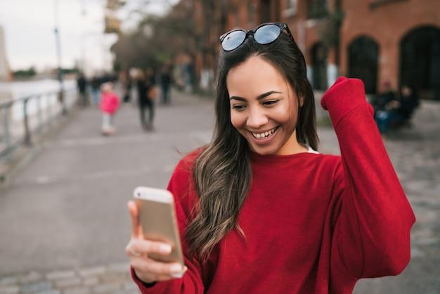 Ritratto di giovane bella donna che tiene il suo telefono cellulare con espressione di successo, celebrando qualcosa. concetto di successo.