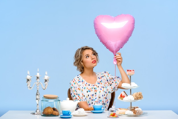 Ritratto di giovane bella donna con i dolci sopra la parete blu