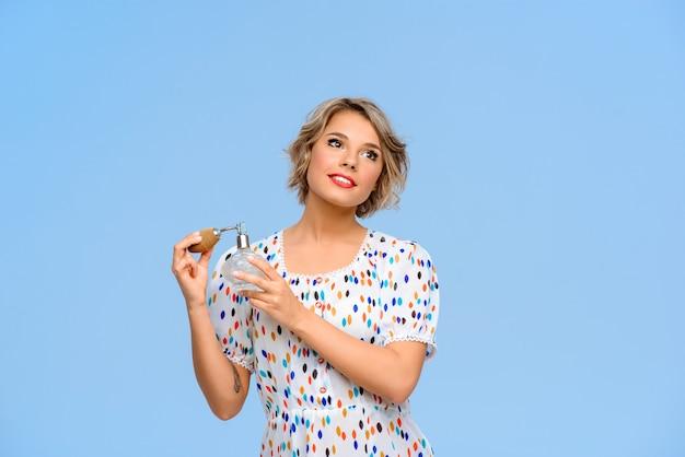 Ritratto di giovane bella donna con profumo sopra la parete blu