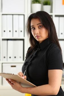 Ritratto di giovane bella donna d'affari bruna lavoro in ufficio
