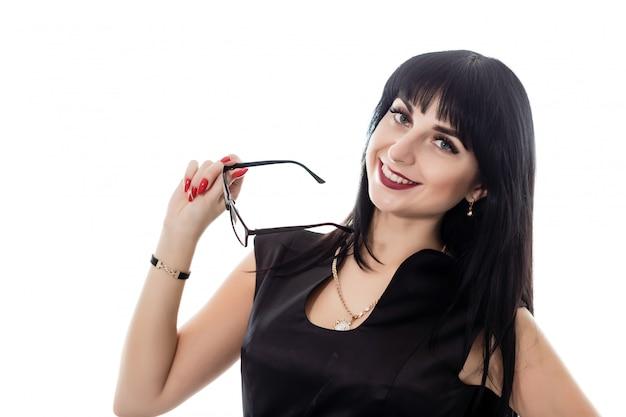 Ritratto di giovane bella donna felice del brunette con gli occhiali che guarda l'obbiettivo