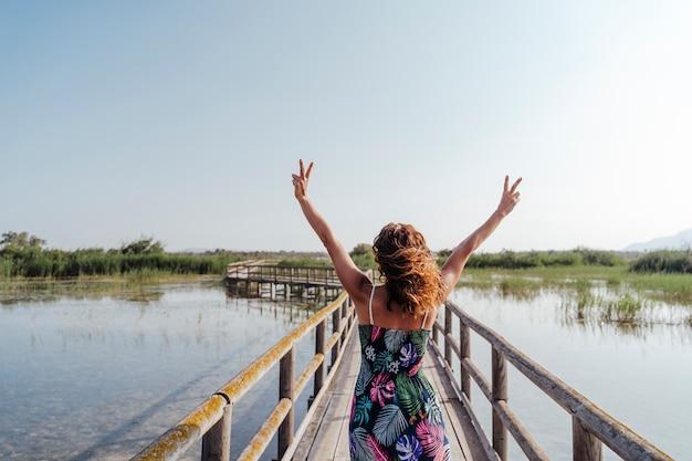 Ritratto di giovane bella donna in piedi su un molo di legno