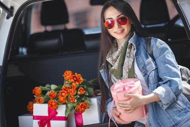 Ritratto di giovane bella donna in primavera che tiene un mazzo di fiori freschi.