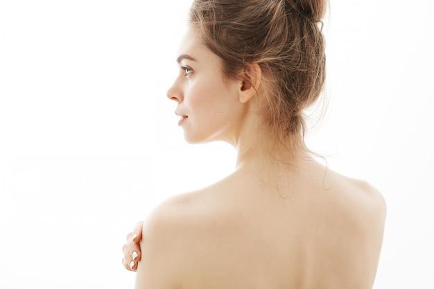 Ritratto di giovane bella donna nuda tenera che controlla fondo bianco.