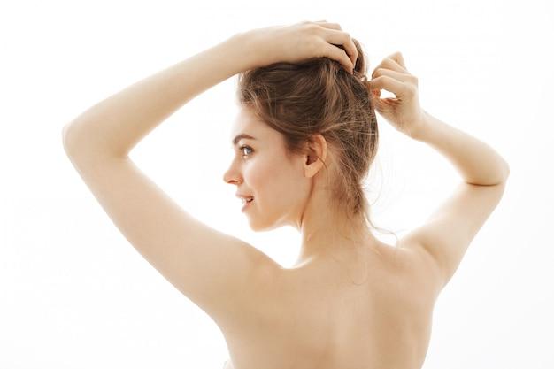 Ritratto di giovane bella donna nuda tenera che corregge panino che controlla fondo bianco.
