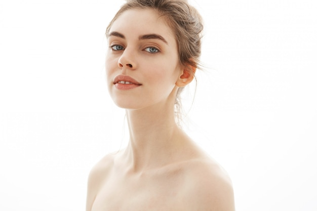 Ritratto di giovane bella donna nuda tenera con il panino sopra fondo bianco.