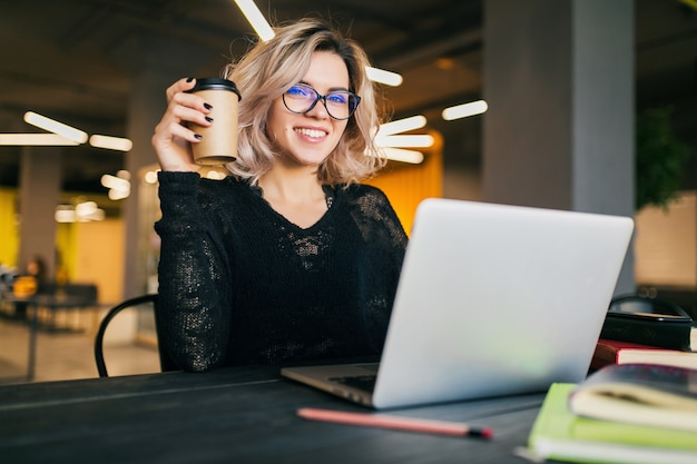 Ritratto di giovane bella donna seduta al tavolo in camicia nera, lavorando sul portatile in ufficio di co-working, con gli occhiali, sorridente, felice, positivo, bevendo caffè in tazza di carta