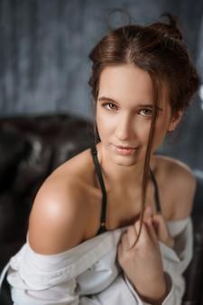 Ritratto di giovane bella donna sensuale in camicia bianca, seduzione