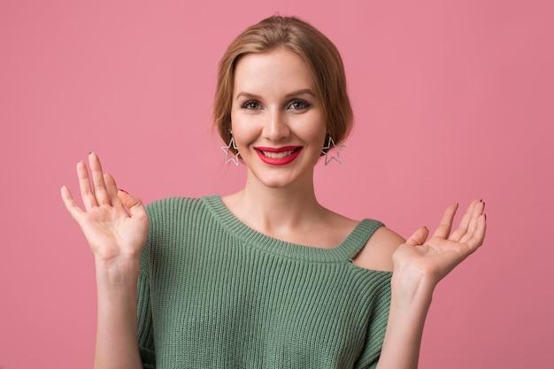 Ritratto di giovane bella donna sexy isolata su sfondo rosa, sorridente, stile elegante, labbra rosse, tendenza della moda primaverile, espressione del viso felice, guardando a porte chiuse, emozione positiva, alzando le mani