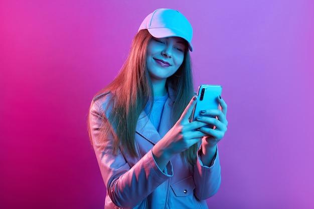 Ritratto di giovane bella modella alla moda indossando panettiere in pelle e berretto da baseball, tenendo il telefono intelligente nelle mani