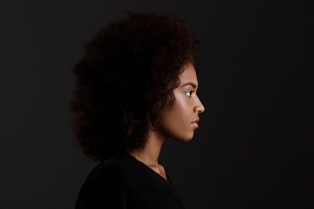 Ritratto di giovane bella ragazza africana sopra la parete scura