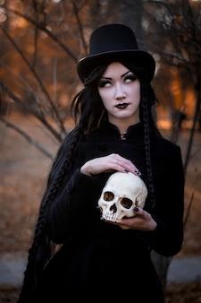 Ritratto di giovane bella ragazza con trucco scuro sul viso e scheletro nelle mani