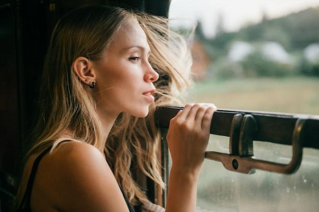 Ritratto di giovane bella ragazza dei capelli biondi che guarda dalla finestra dal treno di guida