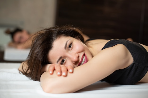 Ritratto di giovane bella ragazza di modello sui lettini di legno che si rilassano in una sauna.