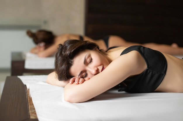 Ritratto di giovane bella ragazza di modello sui lettini di legno che si rilassano in una sauna