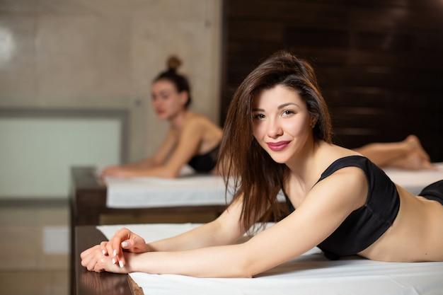Ritratto di giovane bella ragazza di modello sui lettini di legno che si rilassano in uno stile di vita di sauna, di bellezza e di benessere