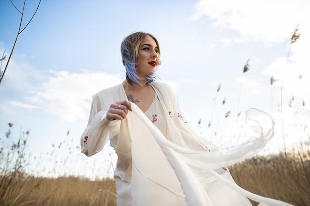 Ritratto di giovane bella ragazza in abito bianco nel campo di grano, a piedi, spensierato.