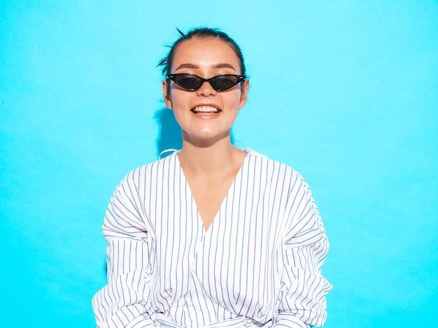 Ritratto di giovane bella ragazza sorridente hipster in abiti estivi alla moda. donna spensierata sexy che posa vicino alla parete blu. modello positivo divertendosi in occhiali da sole