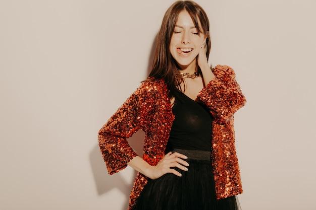 Ritratto di giovane bella ragazza sorridente hipster in abiti estivi alla moda. donna spensierata sexy che posa vicino alla parete in studio. divertimento del modello positivo. mostra la lingua