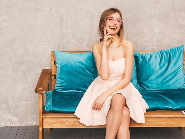 Ritratto di giovane bella ragazza sorridente in abito rosa chiaro estivo alla moda. donna spensierata sexy che si siede sul sofà blu luminoso. in posa in interni di lusso