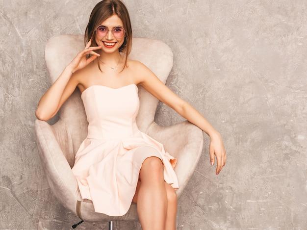 Ritratto di giovane bella ragazza sorridente in abito rosa chiaro estivo alla moda. donna spensierata sexy che si siede sulla sedia beige. in posa in interni di lusso