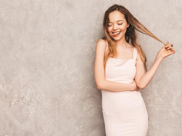 Ritratto di giovane bella ragazza sorridente in abito rosa chiaro estivo alla moda. posa sexy donna spensierata. divertimento del modello positivo