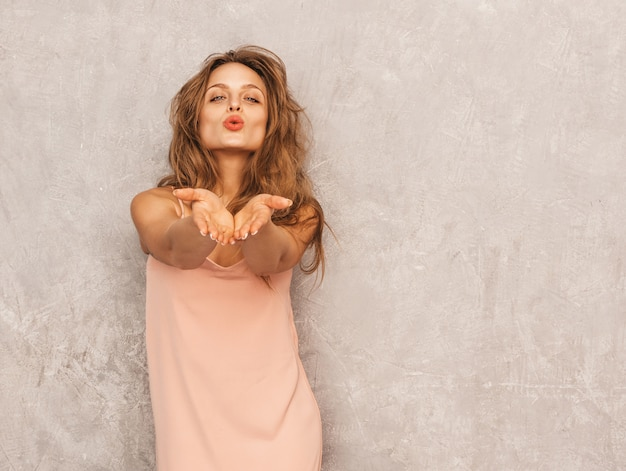 Ritratto di giovane bella ragazza sorridente in abito rosa chiaro estivo alla moda. posa sexy donna spensierata. divertimento positivo del modello. dando bacio dell'aria