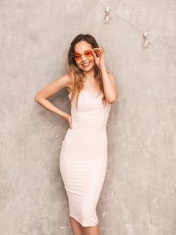 Ritratto di giovane bella ragazza sorridente in abito rosa chiaro estivo alla moda. posa sexy donna spensierata. modello positivo divertendosi in occhiali da sole rotondi