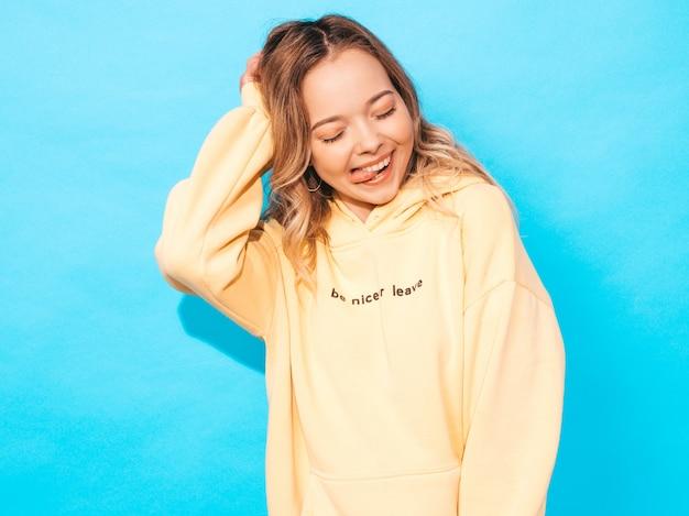 Ritratto di giovane bella ragazza sorridente in felpa con cappuccio giallo alla moda estate hipster