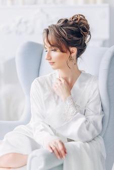 Ritratto di giovane bella sposa in elegante abito bianco seduto su una sedia in un interno luminoso