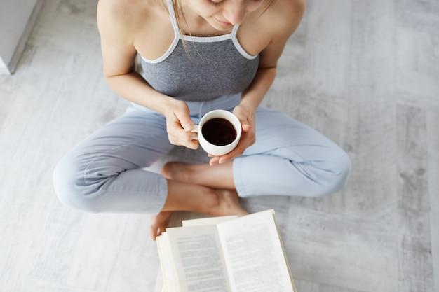 Ritratto di giovane bello libro di lettura tenero della donna che tiene tazza di caffè che si siede sul pavimento sopra la parete bianca.