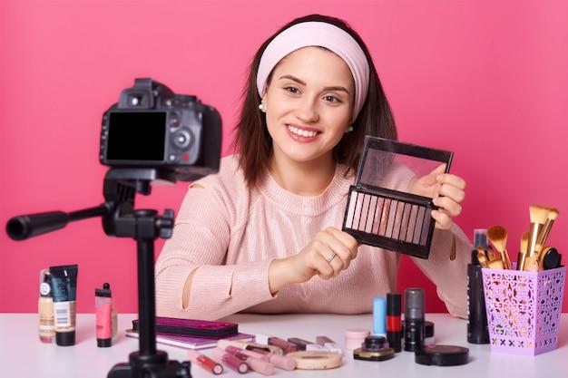 Ritratto di giovane blogger alla moda di successo che si siede davanti alla macchina fotografica