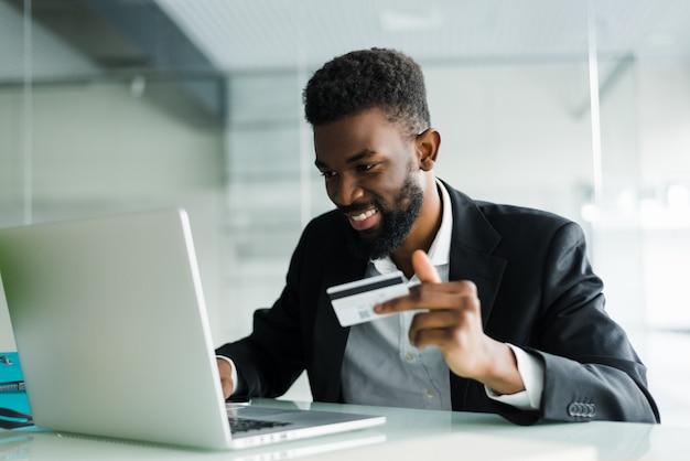 Ritratto di giovane carta di credito africana sicura della tenuta dell'uomo con il computer portatile che paga via internet