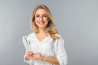 Ritratto di giovane carta e penna bionde sorridenti della tenuta della donna di affari contro il contesto grigio