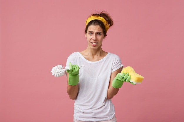 Ritratto di giovane casalinga che indossa la t-shirt bianca, guanti verdi e sciarpa gialla sulla testa che tiene la spazzola e la spugna avente la faccia accigliata che non vuole fare la pulizia