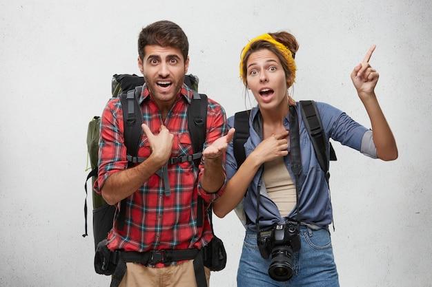 Ritratto di giovane coppia agitata con zaini gesticolano attivamente, cercando di spiegarsi mentre si è in ritardo per l'aereo, con aria preoccupata. linguaggio del corpo. concetto di turismo, viaggi e avventura