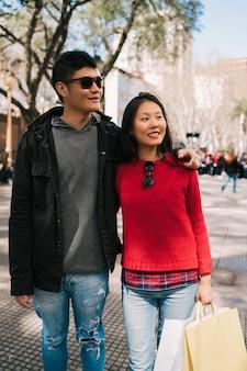 Ritratto di giovane coppia asiatica innamorata che cammina in città dopo lo shopping