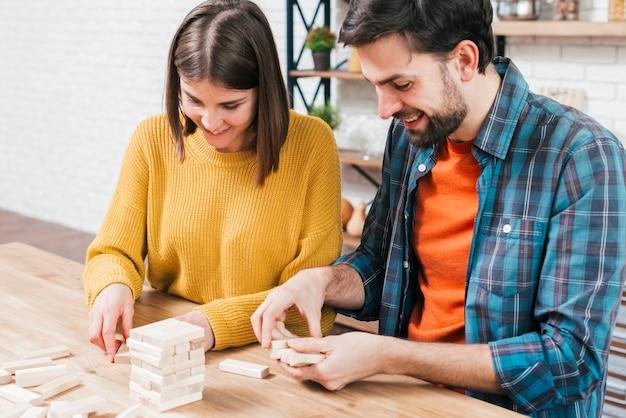 Ritratto di giovane coppia che organizza i blocchi di legno sul tavolo