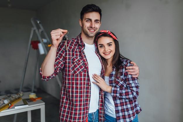 Ritratto di giovane coppia felice casual, tenendo premuto un tasto, comprato un nuovo appartamento