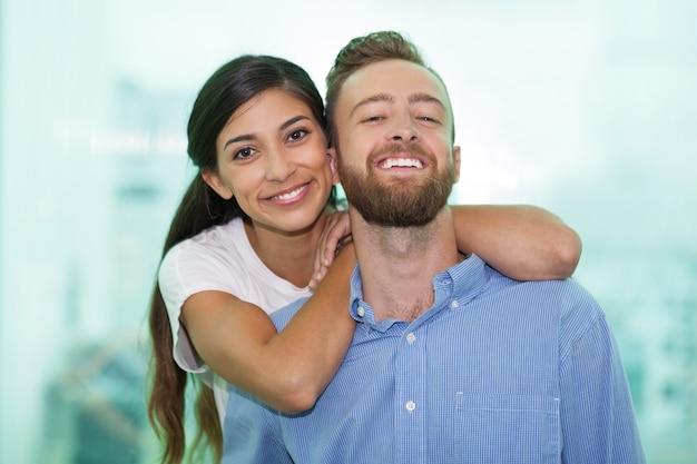 Ritratto di giovane coppia felice sorridente a porte chiuse